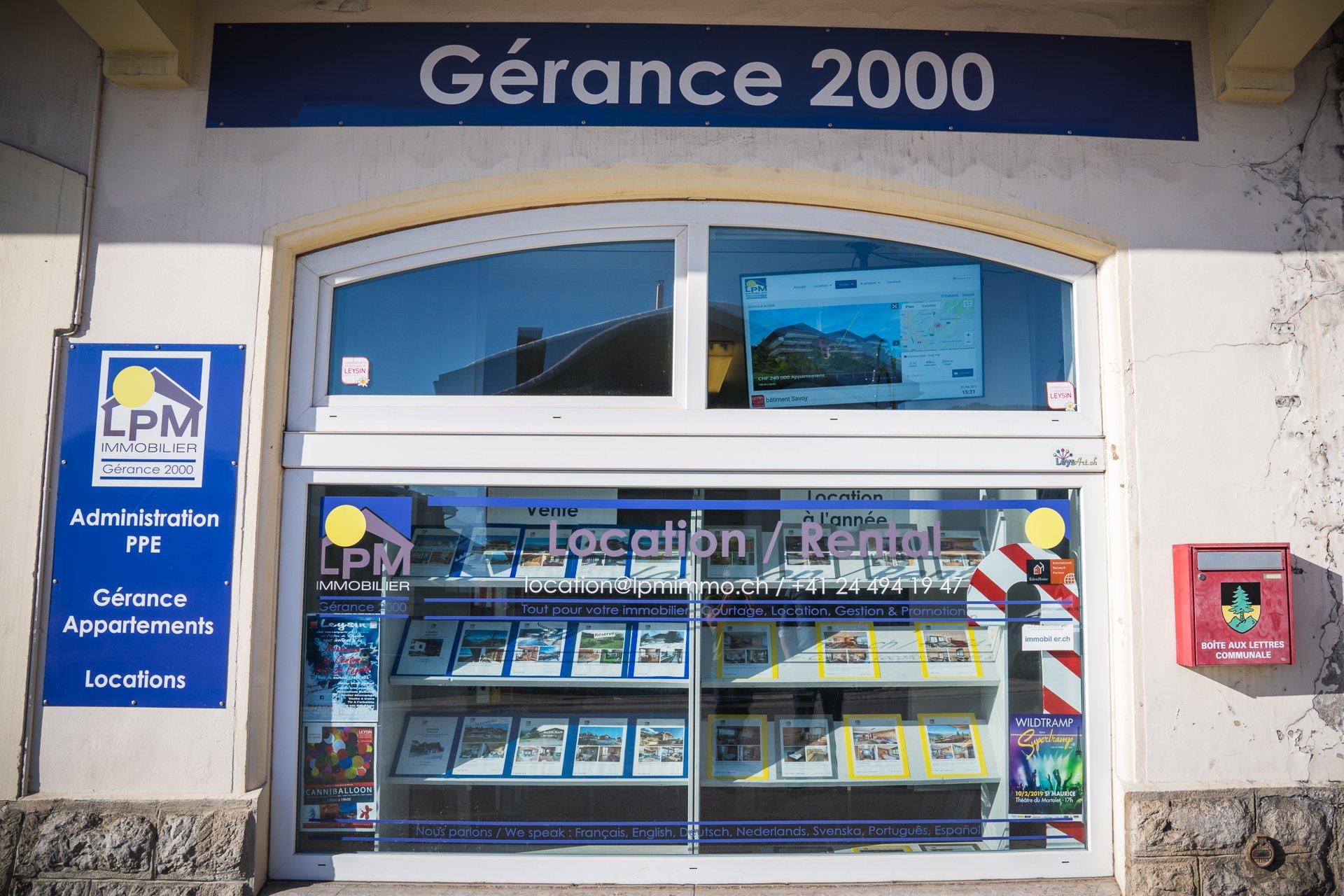 Ecran de vitrine pour agence immobilière avec digital signage. Réseau d'affichage pour région touristique par Pixium.